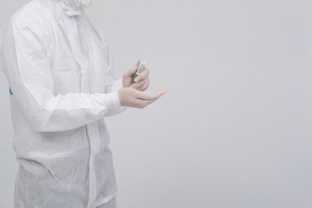 Equipaggi lo scienziato che indossa l'abbigliamento protettivo uniforme biologico, la maschera, i guanti con l'erogatore disinfettante della mano per disinfettare i batteri del virus