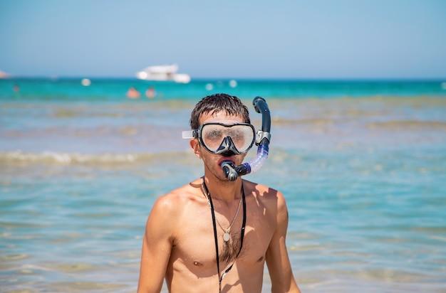 Un uomo al mare con pinne e maschera.