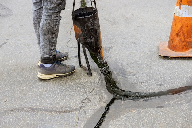 Uomo che sigilla il rivestimento di tenuta del vialetto di asfalto con il fuoco selettivo delle crepe riempite