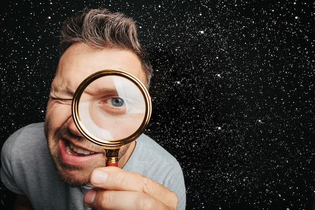 L'uomo vede attraverso la lente d'ingrandimento. grande occhio dell'uomo