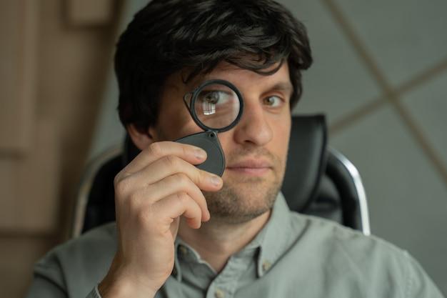L'uomo vede attraverso la lente d'ingrandimento maschio che prende una lente d'ingrandimento e guarda attraverso di essa