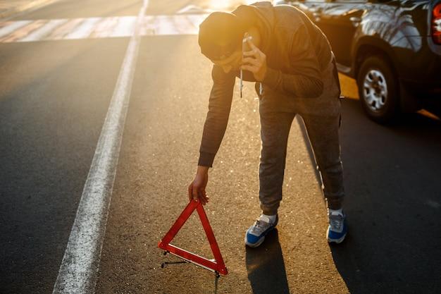 Un uomo crea un triangolo stradale e chiama la polizia o un servizio di auto. incidente stradale