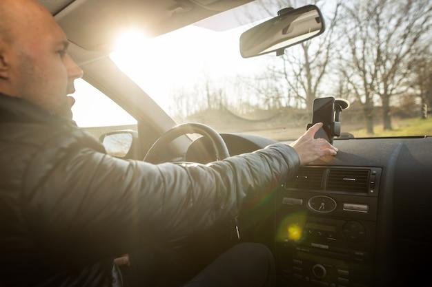 Uomo che imposta il gps sul cellulare prima di guidare, costante durante la guida dell'auto, concetto di trasporto