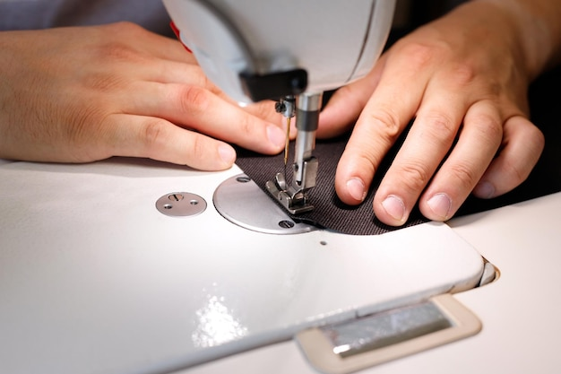 Un uomo che cuce su una macchina da cucire in primo piano