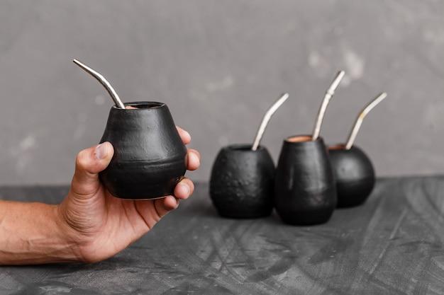 Un uomo che condivide il tè yerba mate nella zucca con cannuccia di metallo sorseggiato