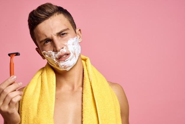 L'uomo si rade il viso con un rasoio con schiuma da barba