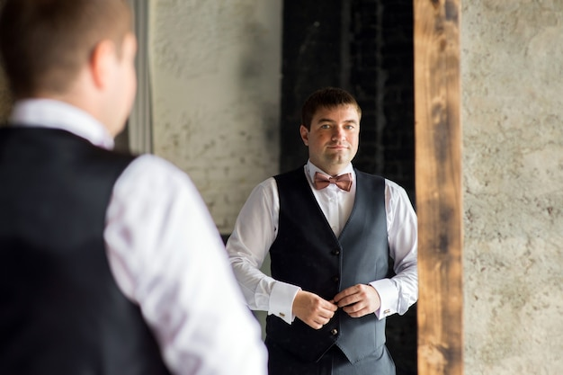 Un uomo con una camicia si abbottona il giubbotto nel riflesso dello specchio