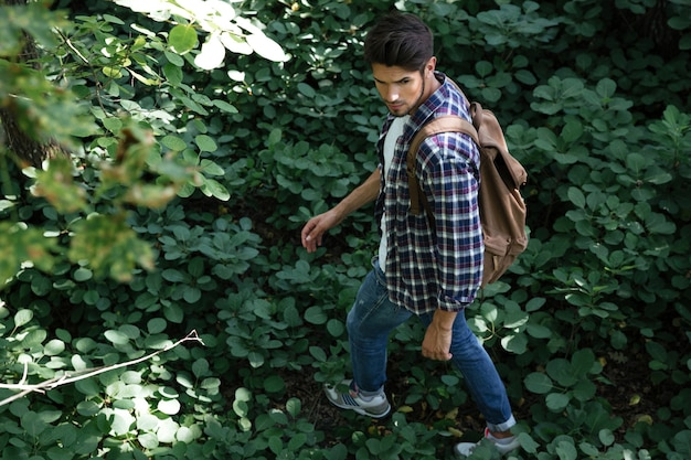 Uomo in camicia nella foresta con zaino
