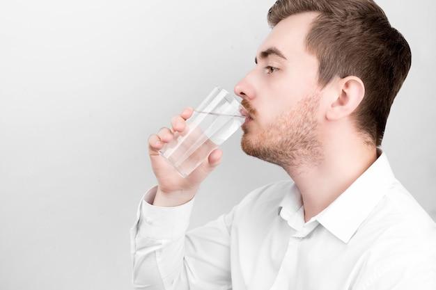 Uomo in camicia che tiene un bicchiere d'acqua. concetto di assistenza sanitaria. acqua dolce. giovanotto. un uomo con una maglietta. concetto di ecologia. l'uomo nella stanza. concetto di bevanda sana. tenendo il bicchiere in mano.
