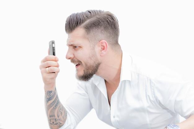 L'uomo in camicia guarda sorpreso lo schermo dello smartphone. concetto di scommesse infruttuose su giochi, fan, ippodromo. tecnica mista