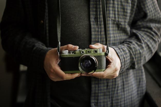 L'uomo nelle mani dell'uomo della camicia tiene il retro orizzontale della macchina fotografica verde del film