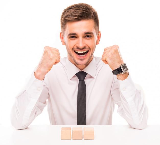 Un uomo in camicia e cravatta si rallegra alzando le mani.