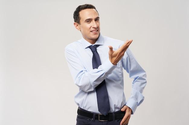 Un uomo in camicia e cravatta mostra con la mano di lato su uno sfondo chiaro
