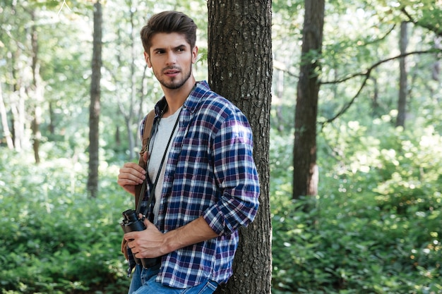 Uomo in camicia con binocolo e zaino vicino all'albero