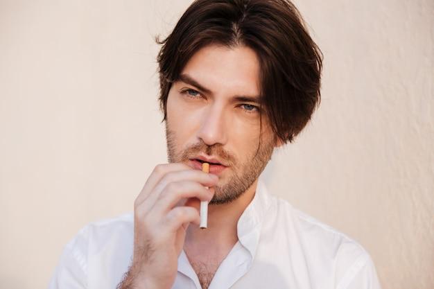 Uomo in camicia con sigaretta. ritratto ravvicinato