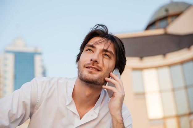 Uomo in camicia con telefono. guardando in alto