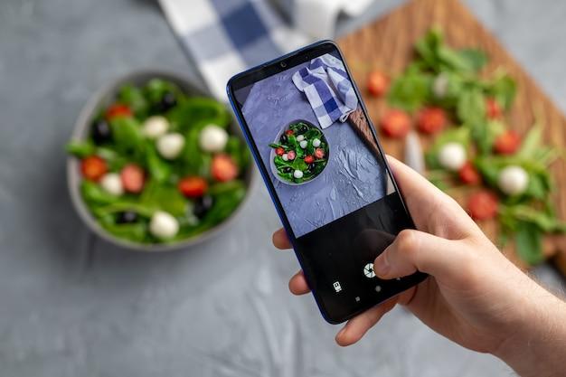 Uomo che spara insalata di verdure fresche con mozzarella e spinaci sulla fotocamera del cellulare. cucinando