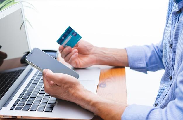 Uomo che fa shopping e paga con cellulare, laptop e carta di credito. copia spazio.