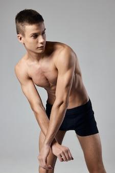 L'uomo in pantaloncini si sporse in avanti modello di mutandine sport fitness.
