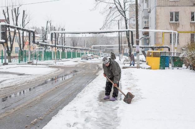 La pala dell'uomo pulisce il marciapiede dalla neve