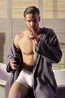 L'uomo mostra il gesto del dito di silenzio con la bottiglia di profumo, segreto. giovane gay attraente in accappatoio in bagno.