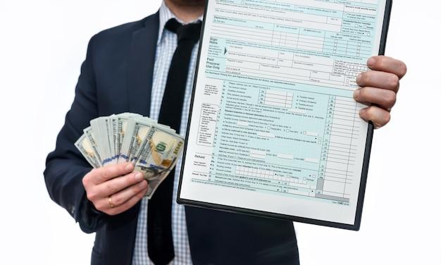 Uomo che mostra 1040 modulo fiscale e dollari in ventola
