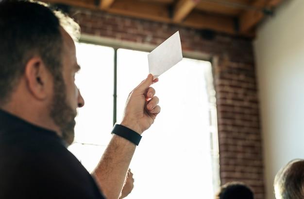 Uomo che mostra il modello di schede in bianco