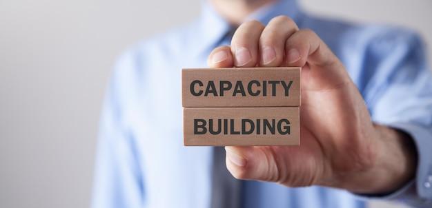Uomo che mostra il testo di rafforzamento delle capacità su blocchi di legno.