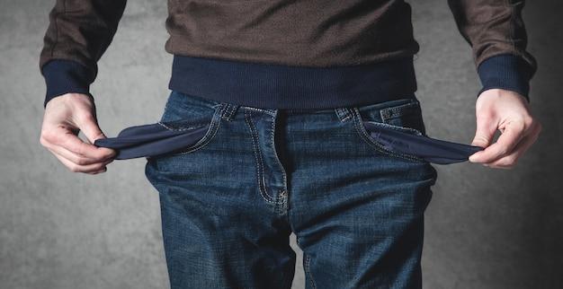 Uomo che mostra tasca vuota. fallimento. senza soldi