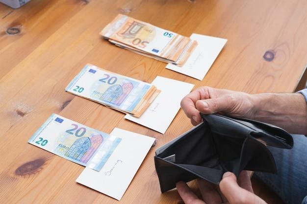 Uomo che mostra portafoglio vuoto dopo aver diviso tutti i soldi per le spese mensili. copia spazio. economia e concetto di crisi.