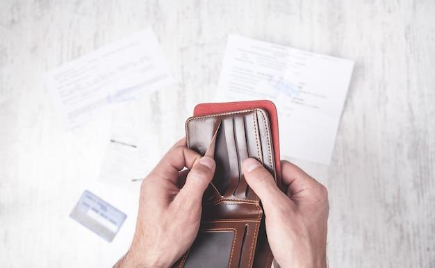 Uomo che mostra portafoglio vuoto. problema finanziario