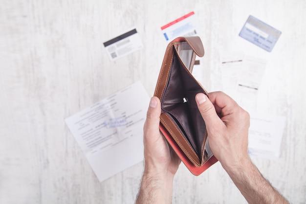 Uomo che mostra portafoglio vuoto