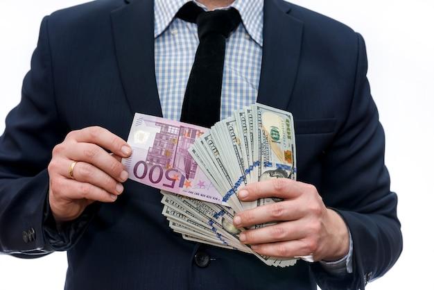 Uomo che mostra le banconote in euro tra il mucchio del dollaro