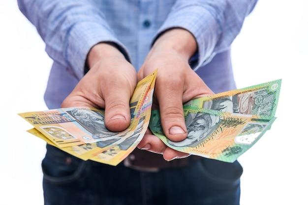 Uomo che mostra fan di banconote in dollari australiani