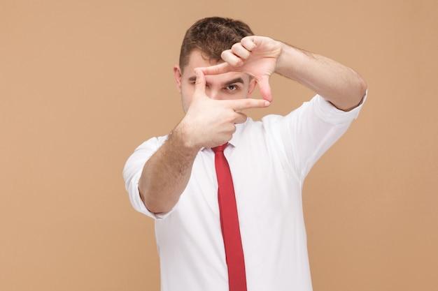 Uomo che mostra il segno del fotografo della cornice alla telecamera