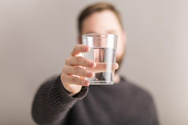 Uomo che mostra un bicchiere d'acqua