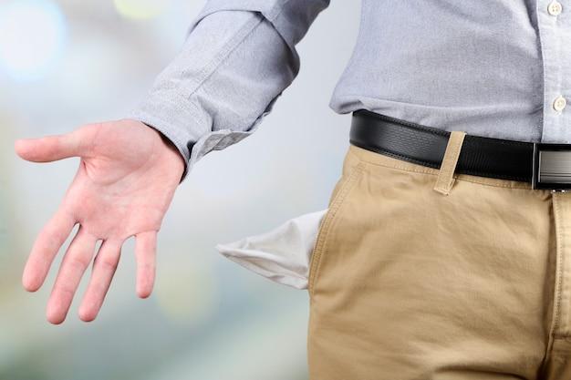 Uomo che mostra la sua tasca vuota su luminoso