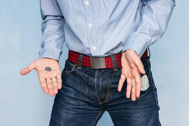 Uomo che mostra la tasca vuota e tiene in mano una moneta. il ragazzo mostra i tuoi ultimi soldi