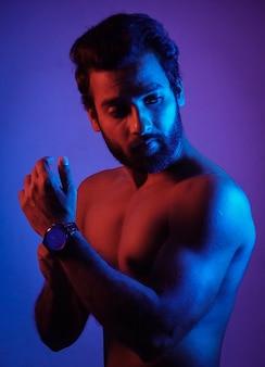 Uomo che mostra il suo orologio con il suo fisico in una luce al neon