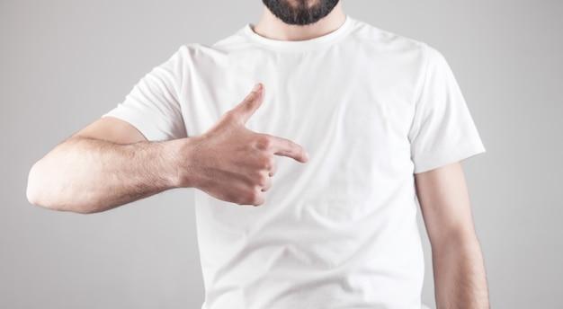 Uomo che mostra la sua maglietta bianca.