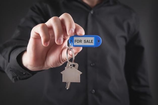 Uomo che mostra la chiave di casa. in vendita