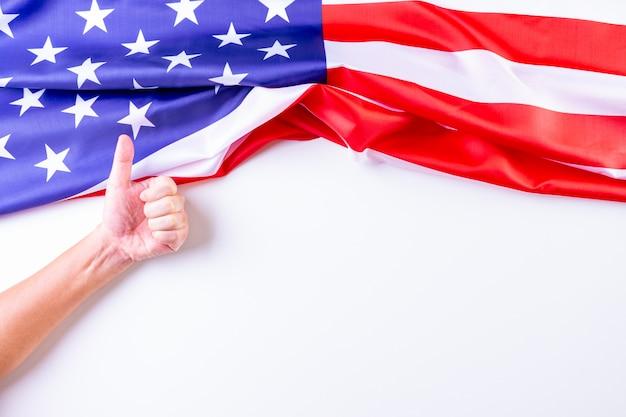 Uomo che mostra i pollici in su sopra le bandiere americane.