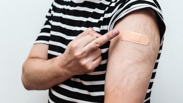 Uomo che mostra il braccio vaccinato. concetto di vaccinazione. persona che mostra il braccio con la fasciatura dopo aver ricevuto il vaccino.