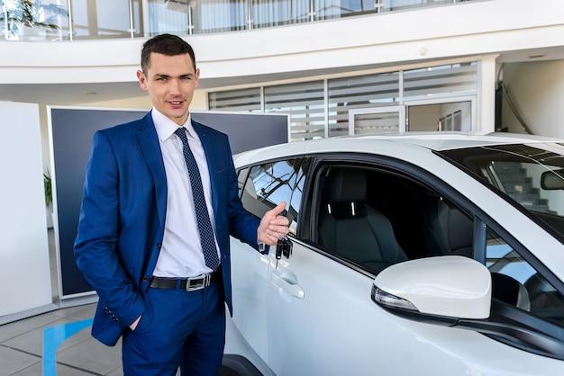 Uomo in showroom con in mano le chiavi di un'auto nuova