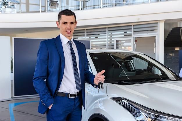 Uomo in showroom con in mano le chiavi di un'auto nuova Foto Premium