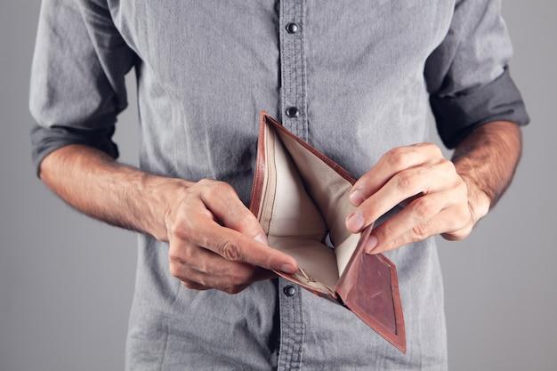 L'uomo mostra un portafoglio di pelle vuoto.