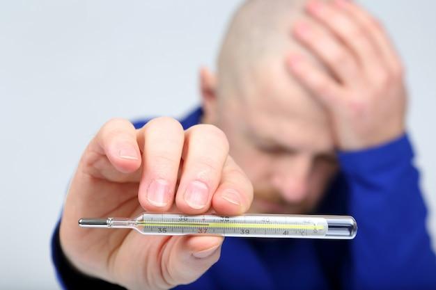 L'uomo mostra un termometro con una temperatura elevata