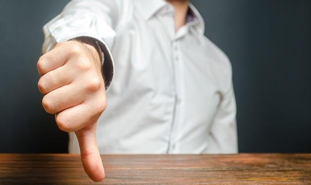 Un uomo mostra un pollice verso il basso. gesto di disapprovazione e rifiuto. valutazione errata, critiche aspre