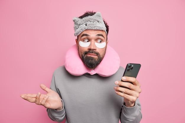 Uomo alza le spalle tiene il cellulare controlla il newsfeed indossa bende sul collo cerotti per cuscino sotto gli occhi