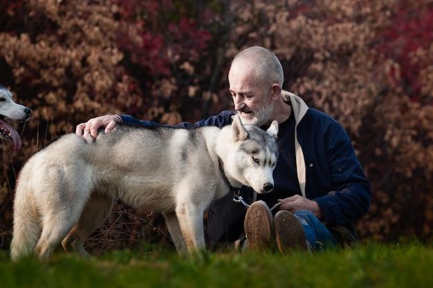 Uomo e siberian husky nel parco